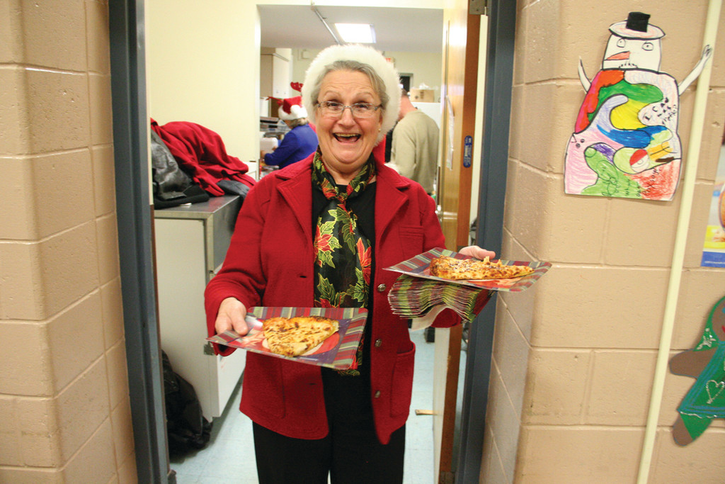 Rotarian Carol Batty serves up the pizza.