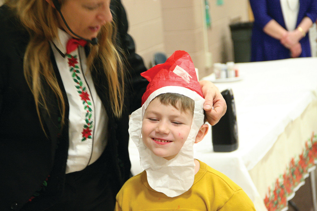 WHAT A LITTLE MAGIC CAN DO: Kyle Sweeney, who helped out with one magic trick, was rewarded with a paper hat that he proudly wore.