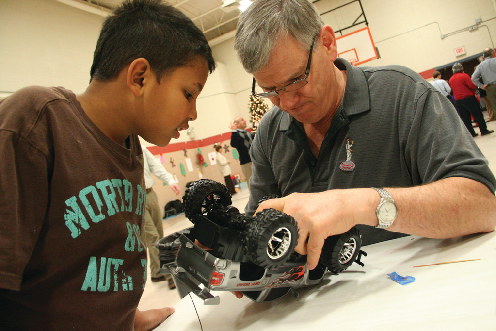 GETTING SOME HELP: Rotarian Steve Hinger helps Elijah Foster prepare the radio-controlled truck he was given for a run around the floor of the all-purpose room at Robertson School.