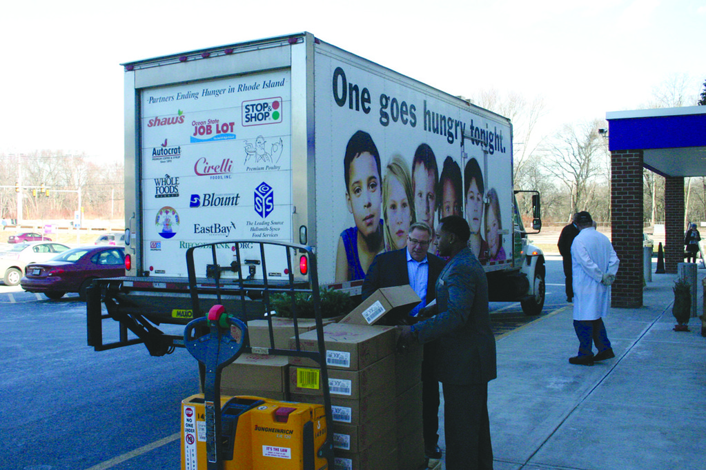 READY TO LOAD: Warwick Avenue Stop & Shop Store Manager Ozzy Monteiro and Joseph Musacchia of Hormel Foods prepare to help load 300 donated hams onto a Rhode Island Community Food Bank truck.