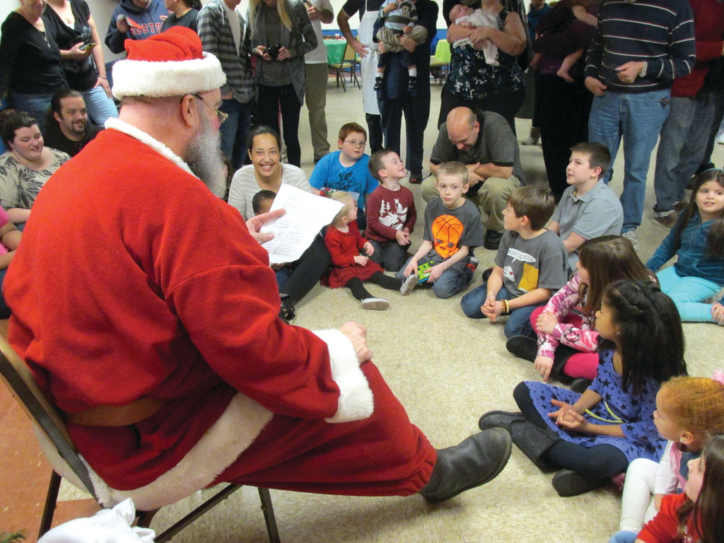 "LEADING THEM IN SONG: Santa Claus, a.k.a. Charlie Greaves, reads the ""'Twas the Night before Christmas"" poem to five-dozen youngsters, who completed verses in unison, during the Tri-City Lodge No. 14's annual Children's Party Sunday in Warwick."
