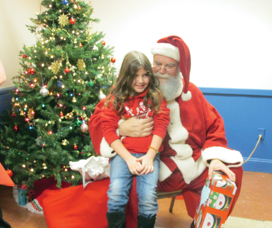 WHAT IT IS ALL ABOUT: Isabel Isherwood, 8, is all smiles as she receives a special present from Santa Claus during the Tri-City Elks Lodge No. 14's annual Christmas Party that provided gifts for youngsters of members and kids from the community.