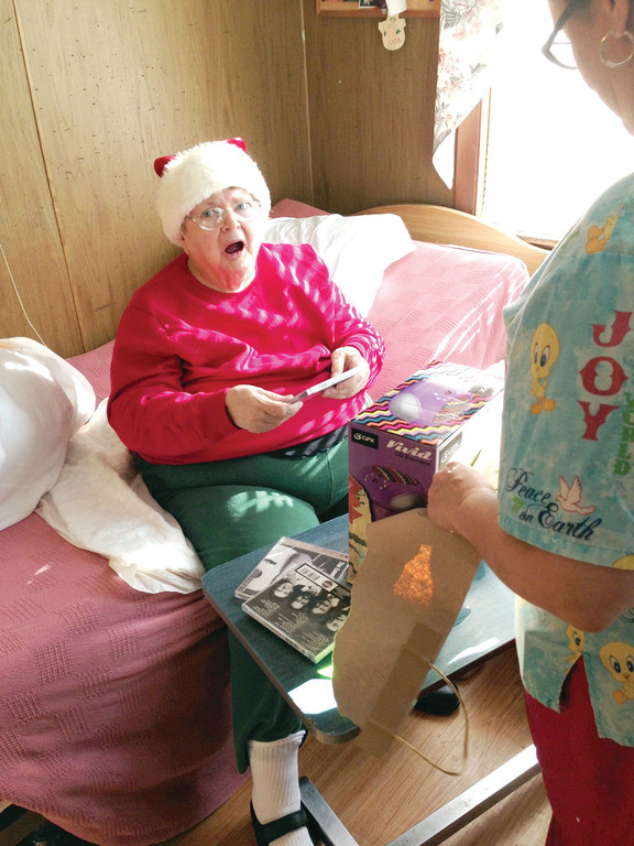 "SURPRISE FROM SANTA: Resident Shirley Carney was shocked when she opened her gift from ""Santa,"" which included a CD player and a number of CDs. According to Giselle Mahoney, who organized the gift-giving project with her mother and sister, Carney told them it was everything she wanted and that they made her Christmas ""very merry."""