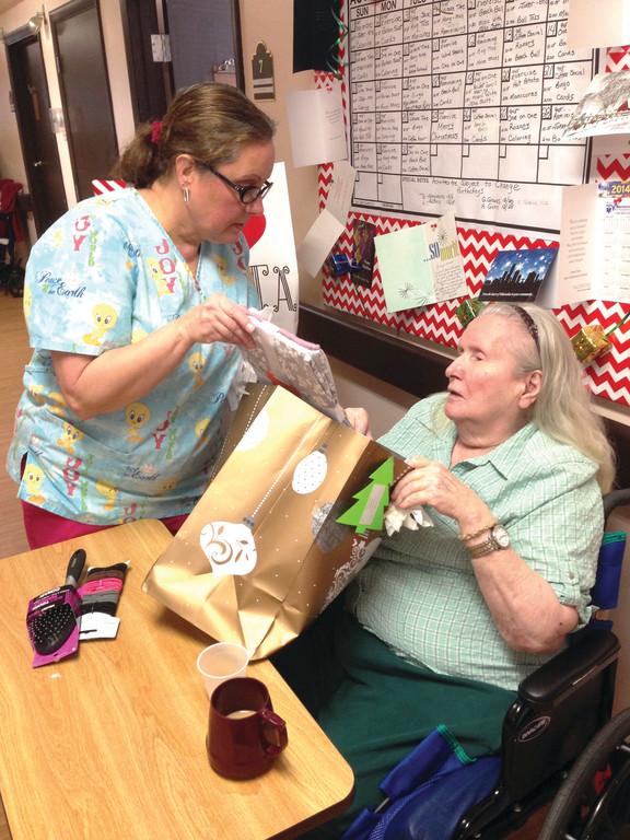 SANTA'S HELPER: Donna LaFrance helps resident Rosemary Pinto open her gift, which included pajamas, nightgowns, a hair brush and hair elastics.