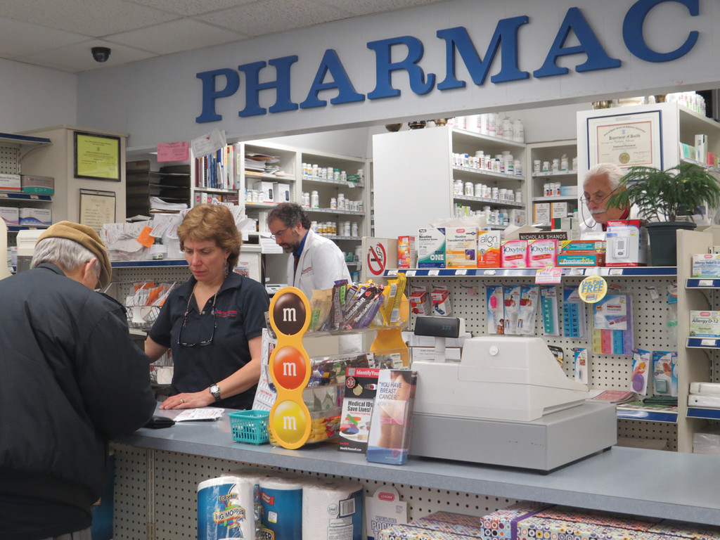 BEST STAFF IN THE WORLD: According to Nick Shanos (back left), the staff at Suburban Pharmacy, which includes Carol Linehan and pharmacist Joe Masso pictured above, is the best in the world. Their first priority is customer service and providing the most personal drug delivery service possible at the city's last independent pharmacy.