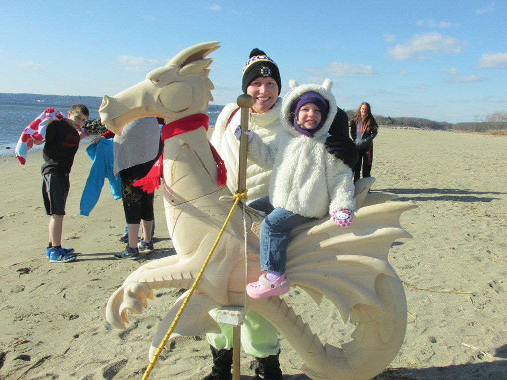 Ella Stevens, 3, sits atop one of the unfinished dobby horses that the Oakland Beach Carousel Foundation had on display during last week's annual Seawall Splash. She's joined by her mother, Andrea Stevens, whose husband Bernie Stevens was among the 26 people who tested their mettle by running into the freezing water that was reported to be 39.7 degrees. (