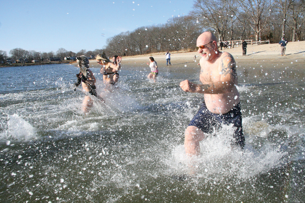 SPLASHING INTO 2014: Dashing into the bay at City Park were those raising funds  at the Pit Bull Plunge.