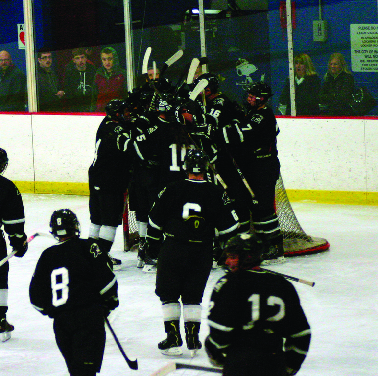 BREAK ON THROUGH: The Pilgrim hockey team celebrates after picking up its first victory of the season on Saturday.