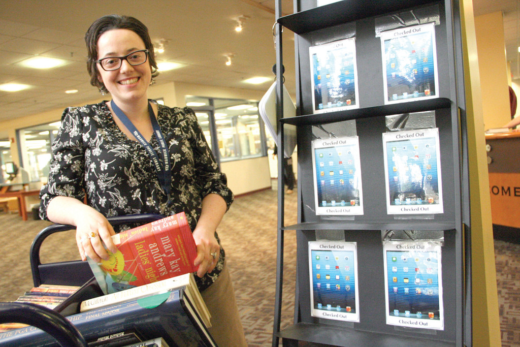 PLENTY OF BOOKS FOR NOW: Jessica D�Avanza, reference librarian at the Warwick Public Library, has a cart full of books, yet the library�s display of e-readers is empty. Some believe the reverse will be true in the years to come.