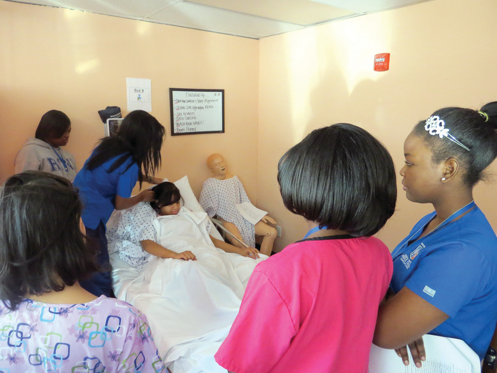 HEALING HANDS: Juniors at Rhode Island Nurses Institute Middle College, the county's only nursing charter high school, have the opportunity to practice their hands-on patient skills during a recent class. The class was practicing to change the dressings on a patient with limited mobility.