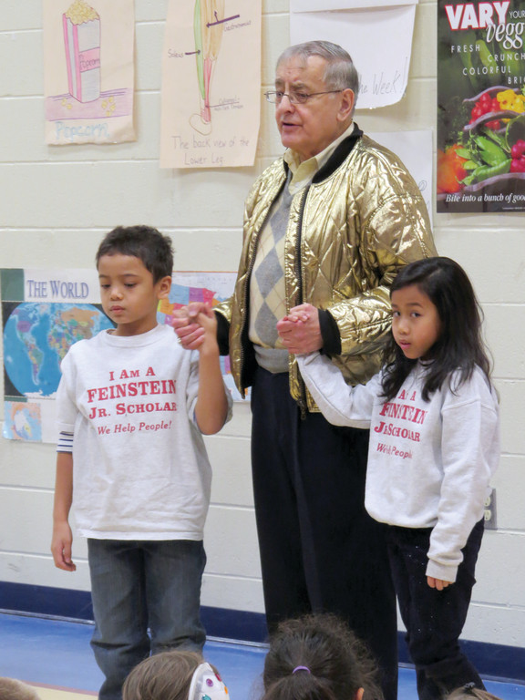 PROUD TO BE A JUNIOR SCHOLAR: Toward the end of his presentation, Feinstein pulled second graders Rangsey Polanco and Katrina Theth up to the front to show off their Feinstein Junior Scholar shirts. He told the students to always wear their shirts with pride.