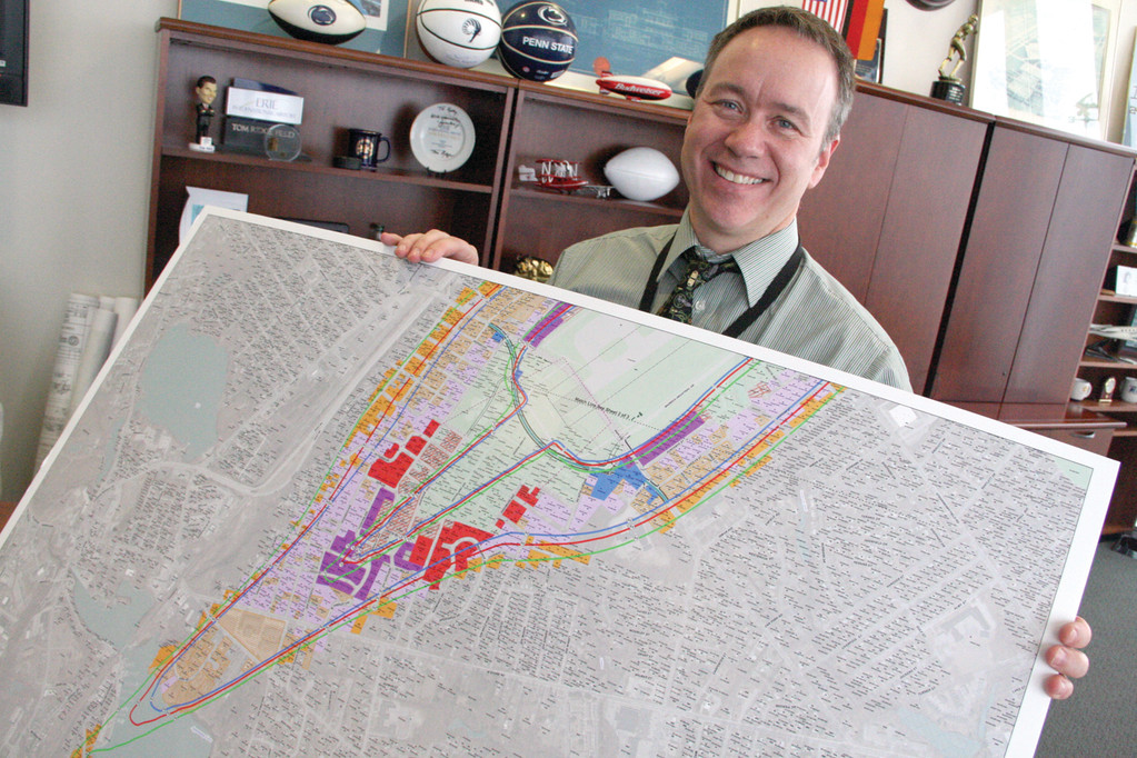 THE CONTOURS: Dan Porter of the Rhode Island Airport Corporation looks over a map defining the noise contours of an extended Runway 5-23.