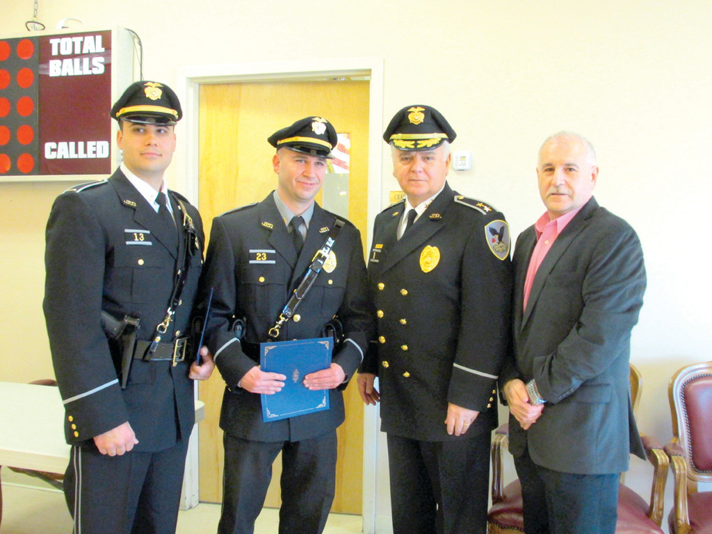 MOVING UP: Johnston's newest promoted police officers, Lt. Mark Vieira, left, and Sgt. Stephen Altomari, second from left, join Chief Richard S. Tamburini and Mayor Joseph Polisena after being sworn in at the Johnston Senior Center.