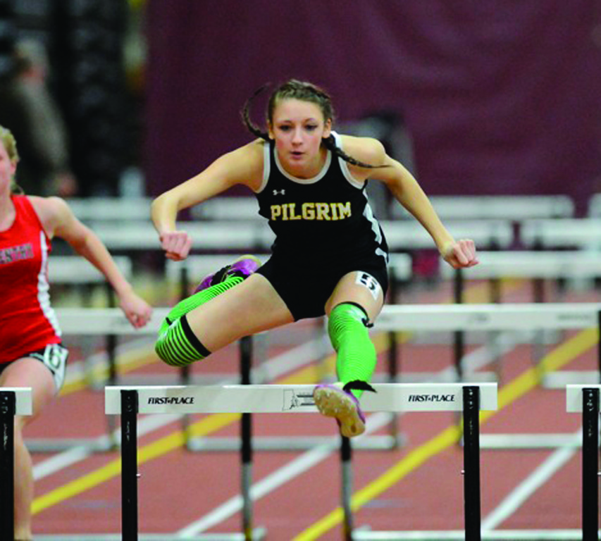 WAY UP HIGH: Melanie Brunelle skies over a hurdle during Pilgrim's regular season finale Thursday. Brunelle starred in wins over Coventry and Woonsocket, winning both the high jump and the 55 hurdles.
