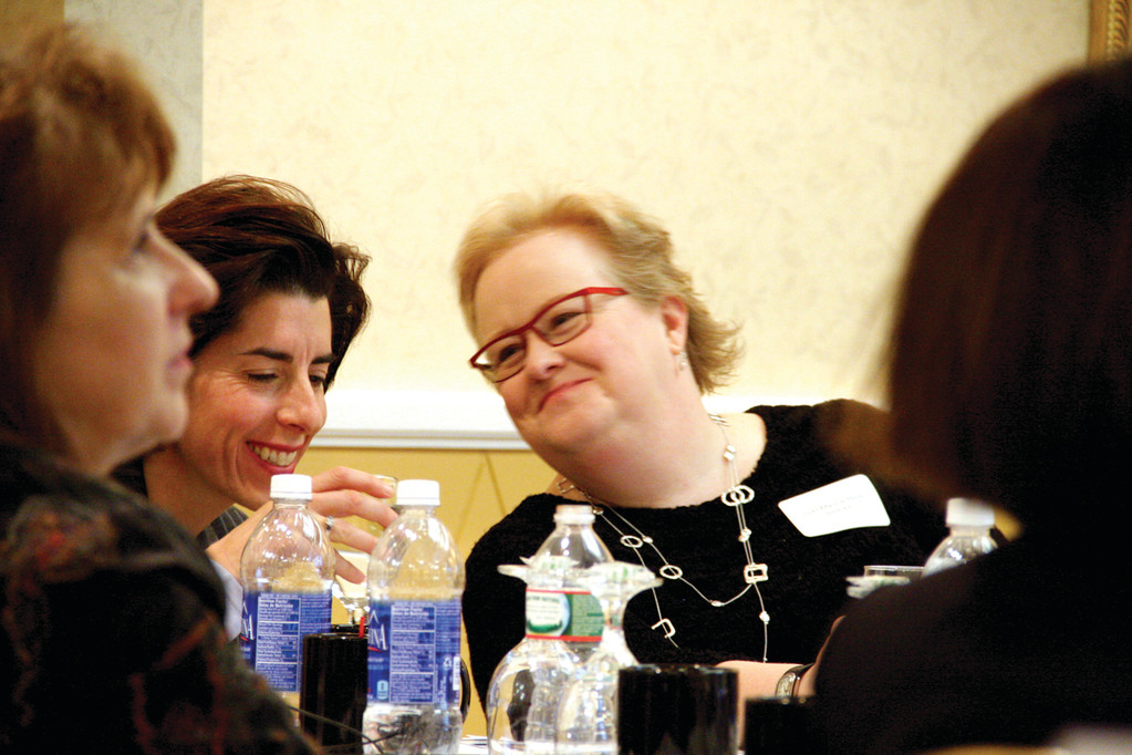 SHARING A MOMENT: General Treasurer Gina Raimondo and Gail Mance-Rios, acting executive director of RIHEAA, talk at Friday's presentation.