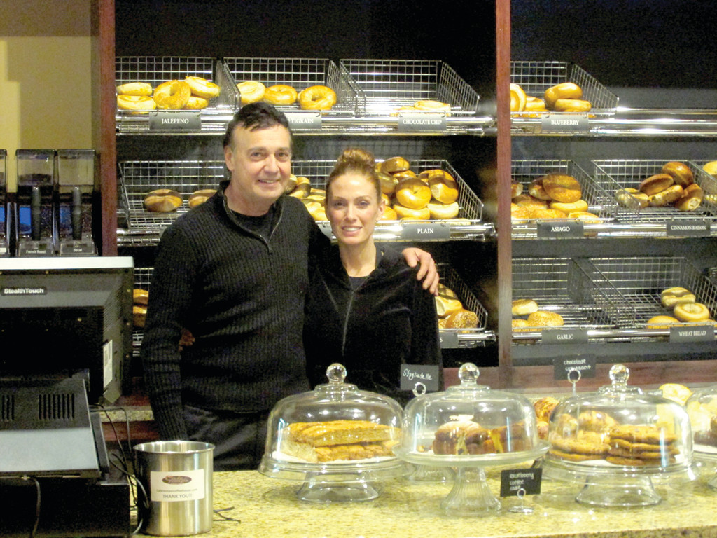 OPEN AGAIN: Tom Buontempo, owner of the former Bagel Factory that's now known as Café Tempo Coffee House, is all smiles as he greets his friend Lori Donnelly in front of a freshly-baked batch of bagels and in front of homemade sweets like Italian biscotti.