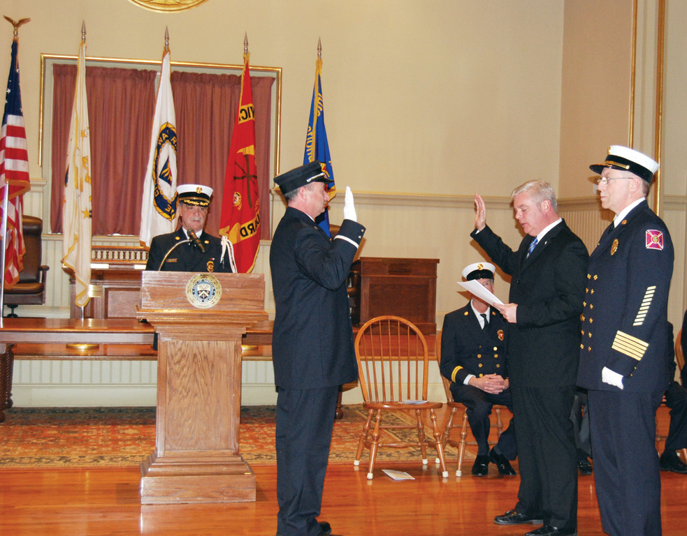 TAKING THE OATH: Mayor Scott Avedisian administers the oath of office to now Lieutenant James Conley of the Warwick Fire Department as Fire Chief Edmund Armstrong looks on.