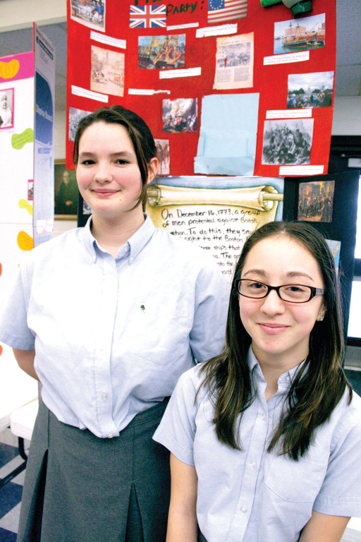 EXHIBITS: Emily Binns, left, did a display on the Boston Tea Party, while her classmate Cora Silvia picked the women's suffrage movement to feature in their history projects.