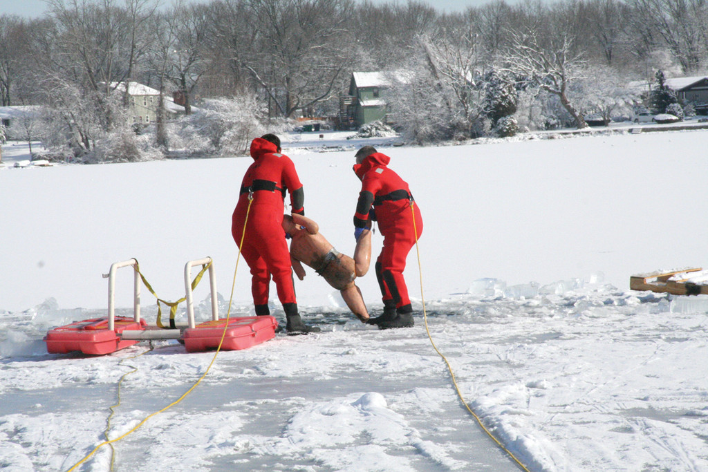 HEAVE HO: Crew members toss a weighted dummy into the icy waters of Sandy Pond.