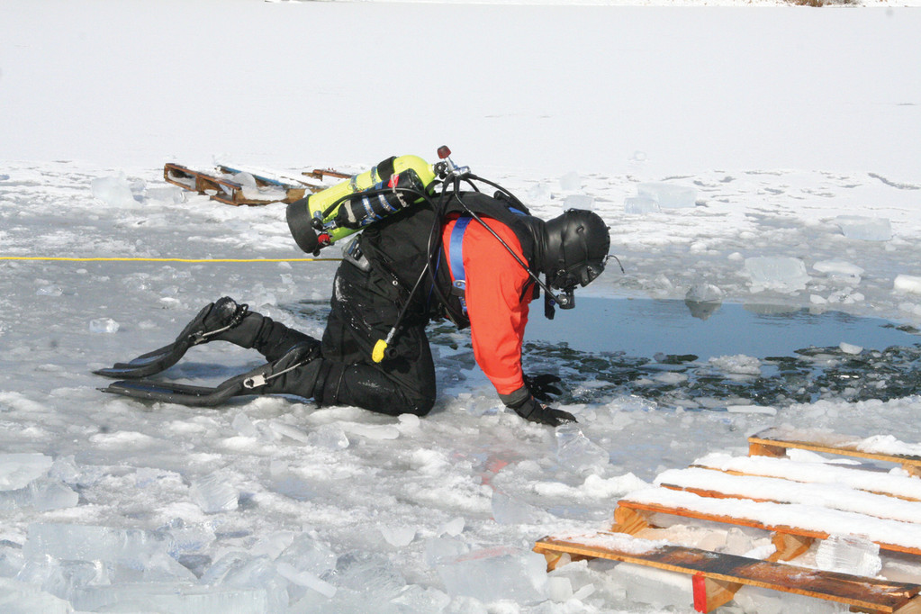 PREPARED TO SLIP IN: Rescue Captain John Faucher slides over to the hole cut in the 6-inch thick ice.