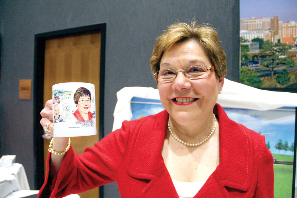 HER OWN MUG: Dr. Kathleen Hittner displays the mug given her from the staff at the Rhode Island Airport Corporation. The caricature on the mug is a smaller version of a drawing done in her honor by artist Frank Gallaso.