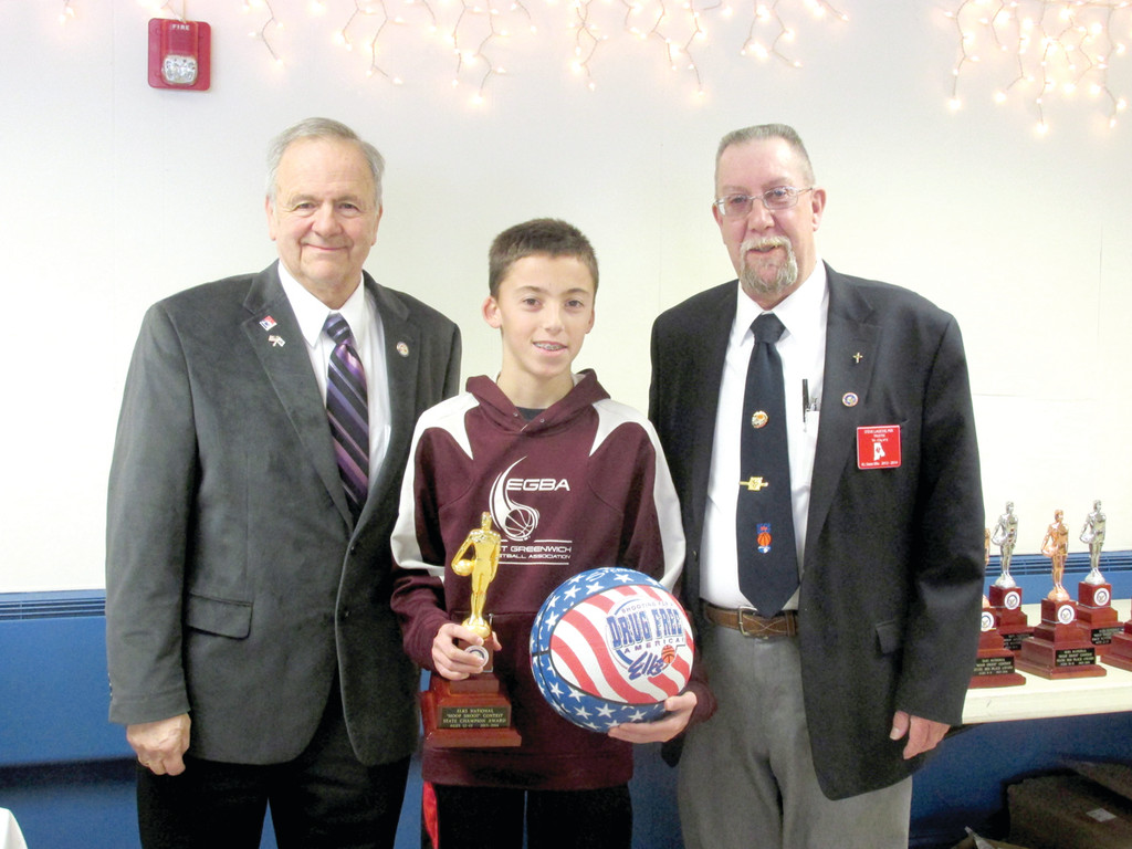 REPRESENTING RI: Justin Grenier, 13, who represented Tri-City Elks Lodge No. 14 and won Saturday�s competition, holds the R.I. State Championship Trophy and special basketball he received from Richard P. Blinn (left), regional director from Haverhill, Mass., and Steve Lagesse of the Warwick-based Lodge.