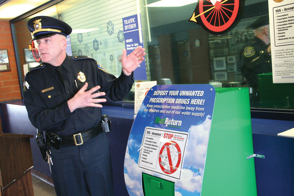 NO NEED TO WAIT: Warwick Police Capt. Joseph Coffey stands with the prescription drug take back bin within the front door to police headquarters. Until now, residents had to wait for a drug take-back drive to rid themselves of unneeded or outdated prescription drugs.