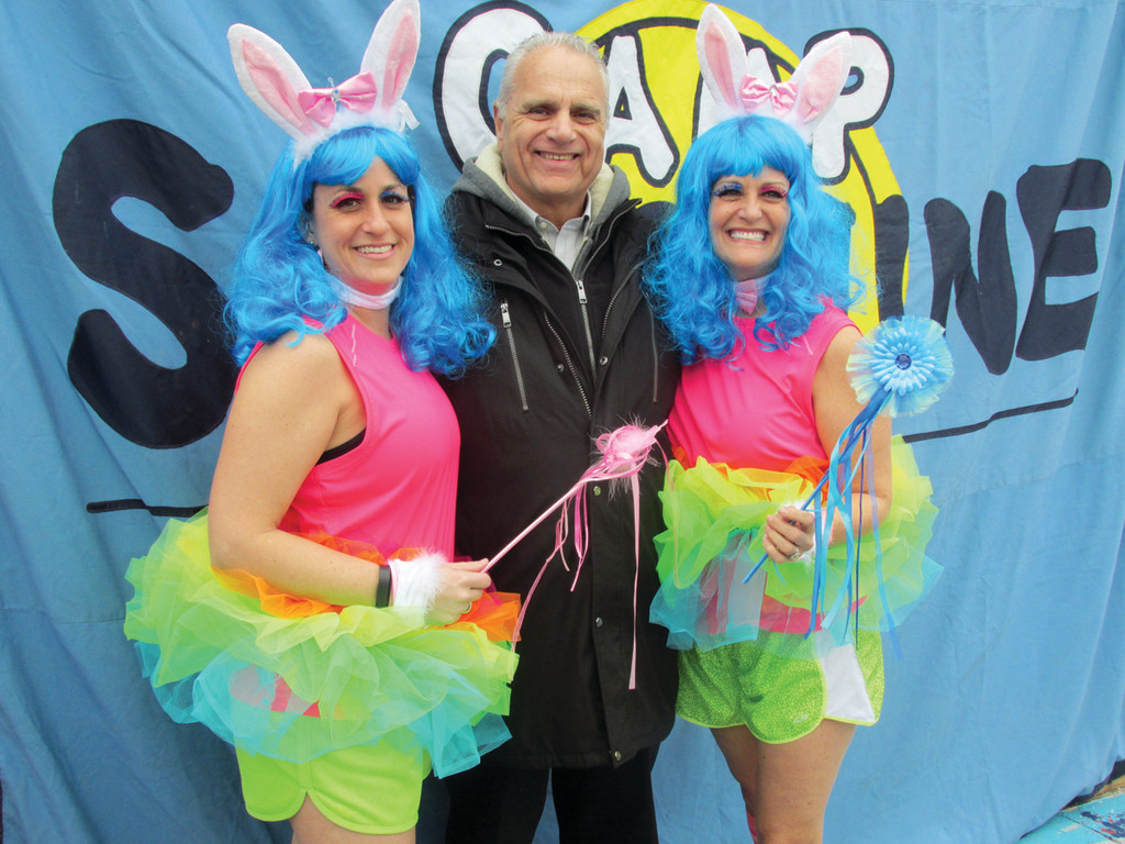 STAYING DRY: Warwick City Ward 5 Councilman Ed Ladouceur enjoys a lighter moment with Twinkle Toe Ballerinas and his Warwick Neck neighbors Christina Henriques (left) and her sister Becky Henriques, who were the driving force behind the success of Saturday's second annual Polar Dip that netted upwards of $25,000.