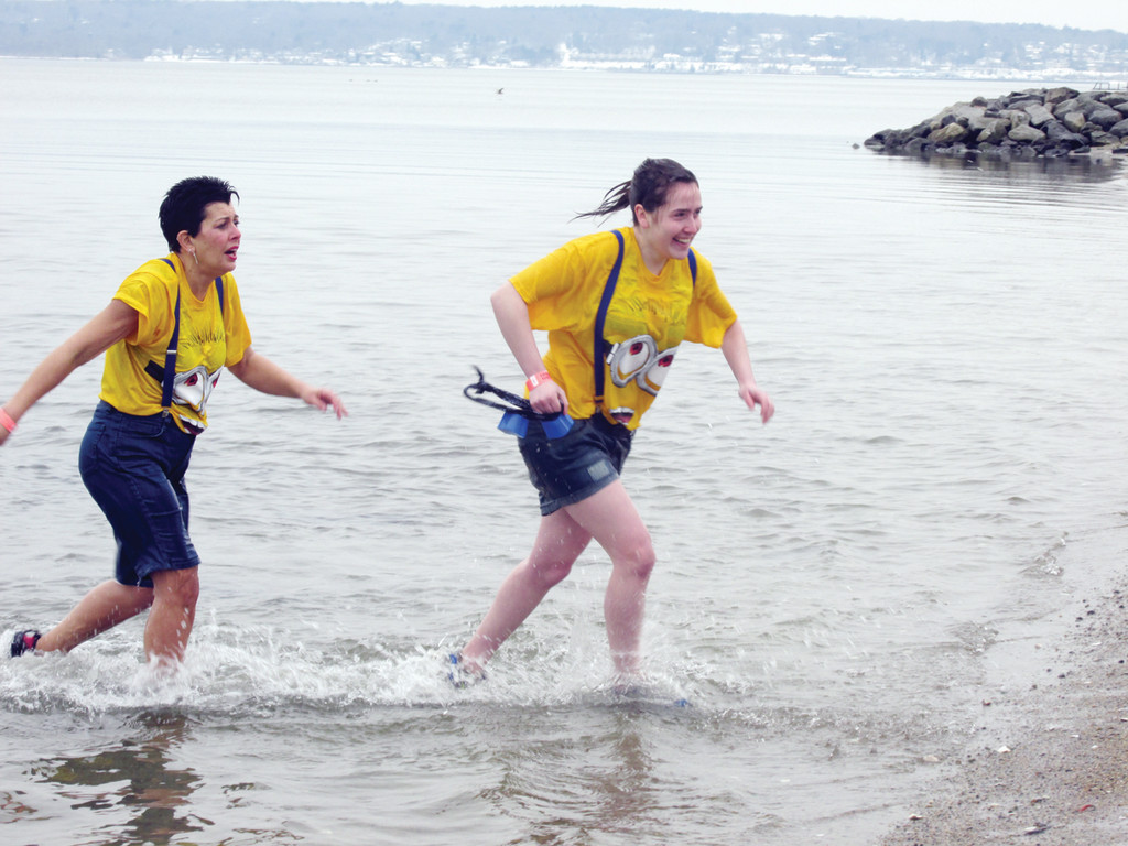 "DRESSED FOR A DIP: Wearing yellow T-shirts and black shorts, Patti and Rebecca Hickey didn't mind ""freezin' for a reason"" during Saturday's second annual R.I. Polar Dip in Warwick."
