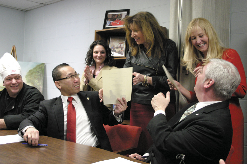 MEAL DEAL: Cranston Mayor Allan Fung, left, and Warwick Mayor Scott Avedisian hand copies of the newly-signed agreement on senior meal preparation to Susan Stenhouse and Meg Underwood – the directors of the cities' respective senior centers – during a Feb. 14 press conference and signing ceremony.