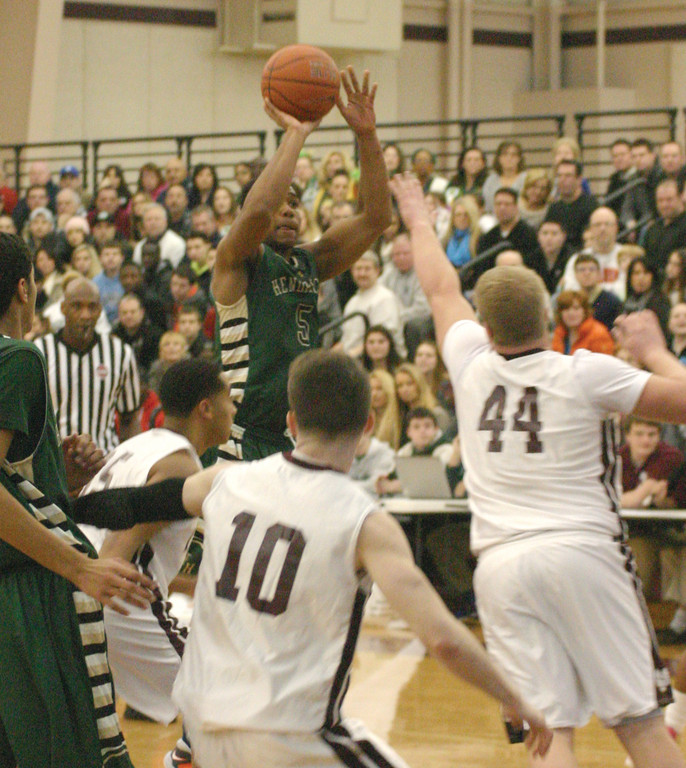 Garfield Coustard rises up for a jumper with a hand in his face.