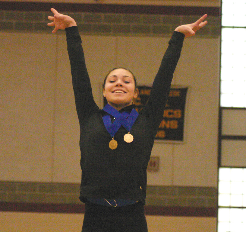 CROWDED AT THE TOP: Vets junior Candis Kowalik salutes the crowd after winning the individual gymnastics state title.