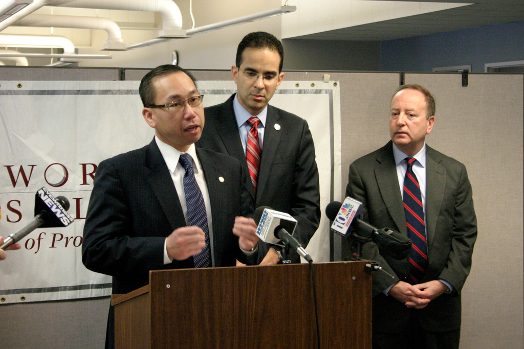 Cranston Mayor Allan Fung speaks as Providence Mayor Angel Taveras and Robert Ricci, administration at Workforce Solutions of Providence and Cranston, look on during the announcement of the 2014 Mayors' Job Fairs.