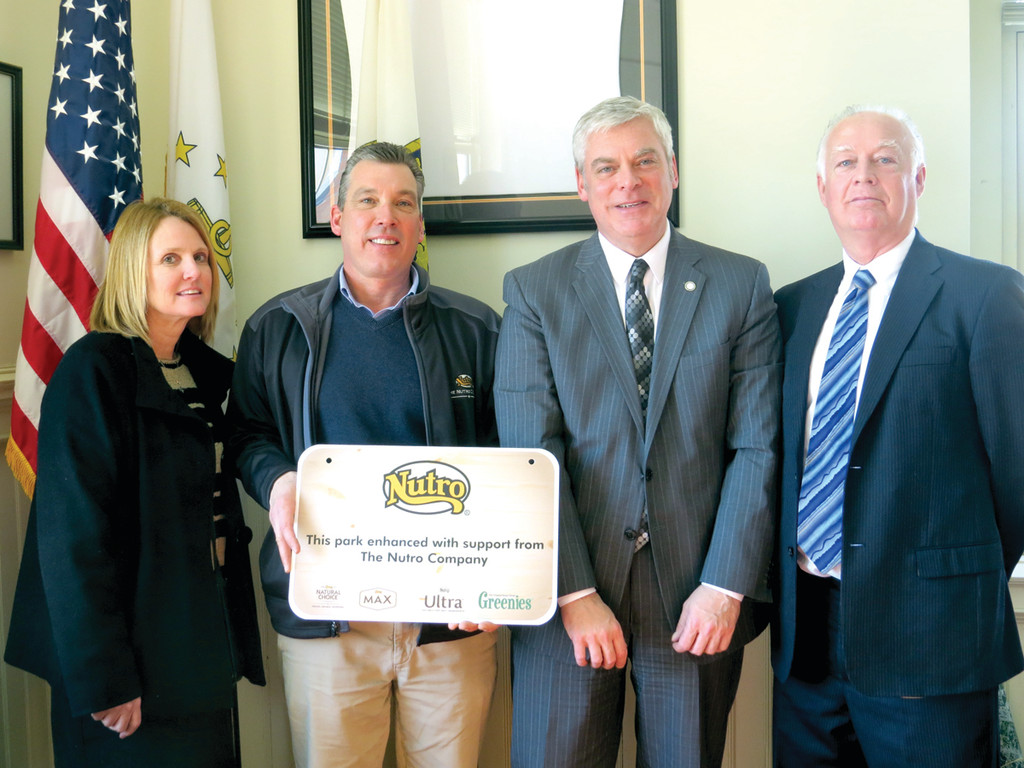 FOR THE DOGS: Patti Timmons and Wayne Renfrew of Nutro Products Inc. present Warwick Mayor Scott Avedisian and Director of Parks and Recreation Mickey Rooney with a sign to display in the dog park at City Park to recognize their $2,000 grant, which was recently obtained thanks to a group of dedicated Warwick dog owners.