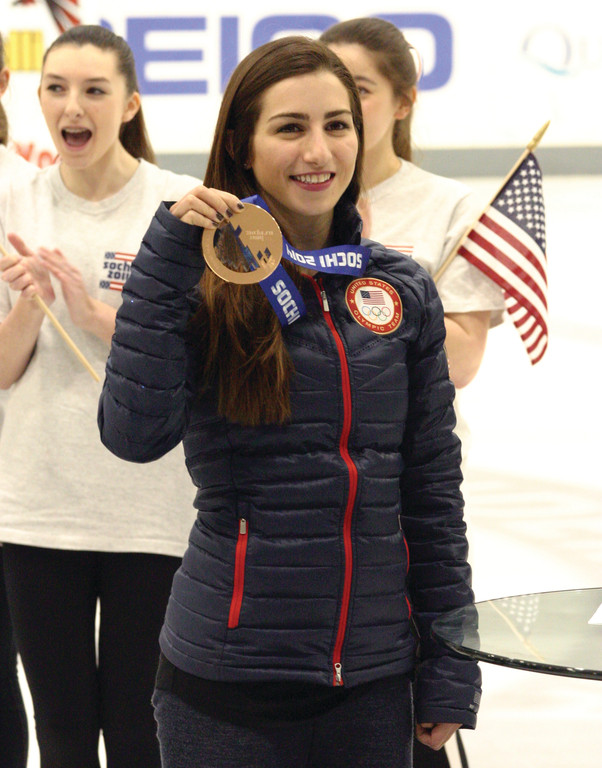 WELCOME BACK: Cranston native Marissa Castelli shows off her Olympic bronze medal to the crowd at Providence College�s Schneider Arena during Monday�s homecoming celebration.