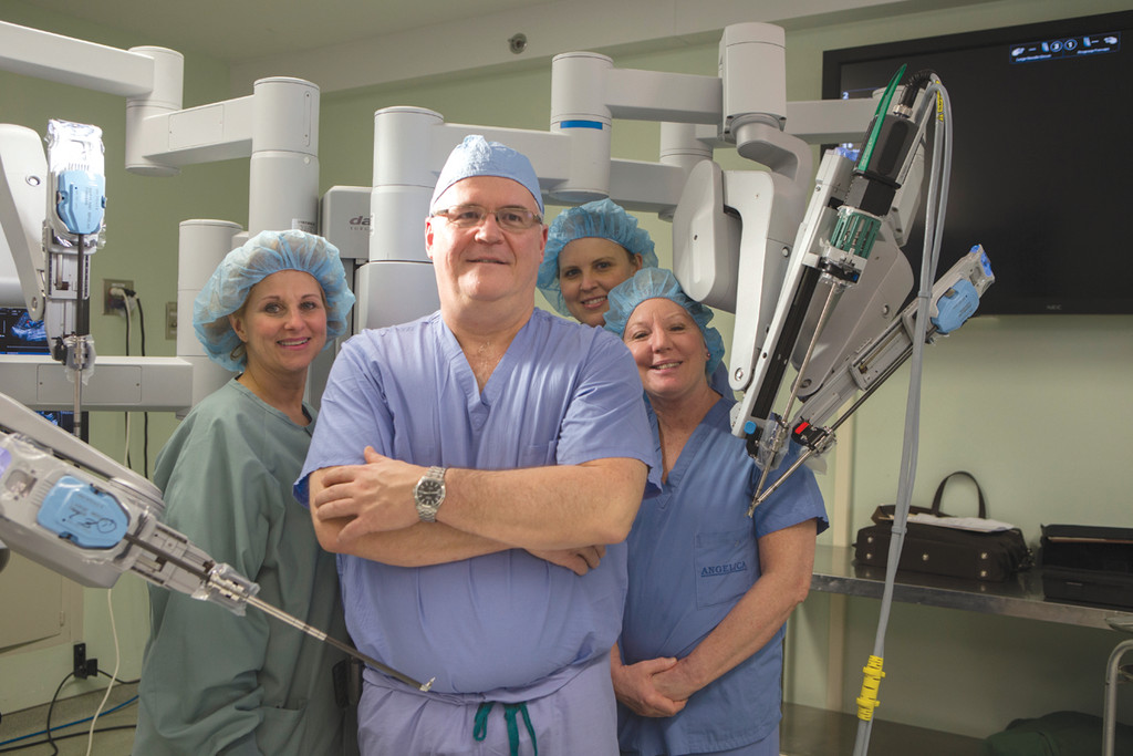 KENT WELCOMES DA VINCI: Linda Lagasse, RN, Dr. Joseph Brady, Apryle Kuznicki, and Cheryl Hall, ORT show off Kent Hospital's new da Vinci SI surgical robot, which is used to perform gallbladder removals and other urological procedures at the hospital.