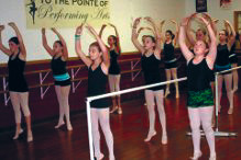 A bevy of joyful aspiring ballerinas smile for the camera at To the Pointe of Performing Arts.