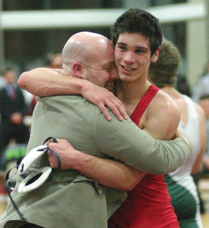 BIG MOMENT: Aaron Travers shares a hug with head coach Jerry Sabatelli after winning the championship in the 145-pound weight class.