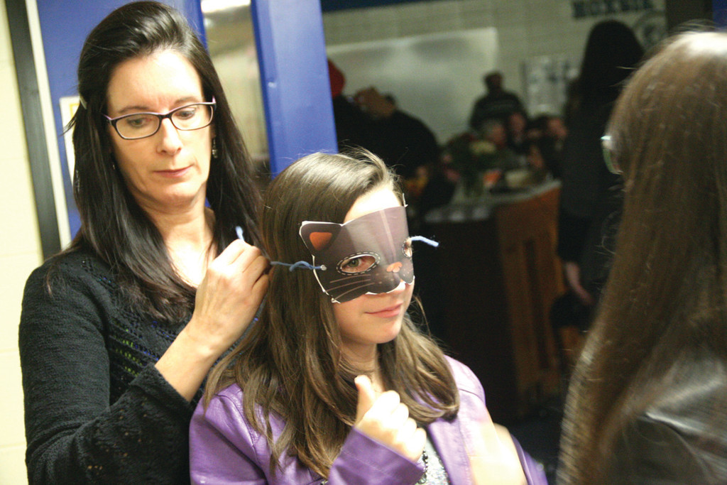 A CAT IN THE MAKING: Meredith Andreozzi helps Olivia Martinelli with her mask in preparation for her appearance on stage.