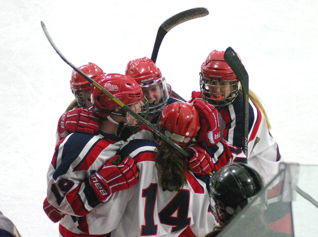 Players from the Warwick girls' hockey team celebrate after Madison Balutowski's empty-net goal clinched a victory in Monday's winner-take-all semifinal game against Bay View. The Lady Titans won 4-1, and will now take on La Salle for the state championship.