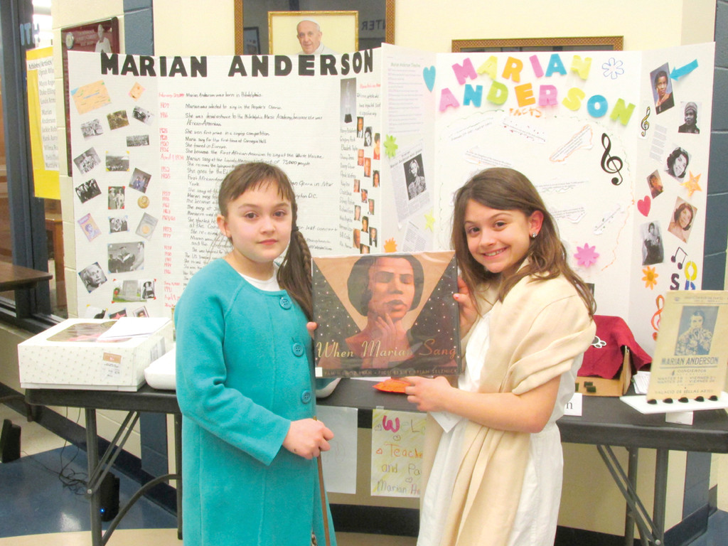 RICH HERITAGE: Thalia Spardello, left, and Mia Ducharme stand in front of the display they created about famous African American singer Marian Anderson for last Thursday's Black Heritage Museum at Immaculate Conception Catholic Regional School in Cranston.