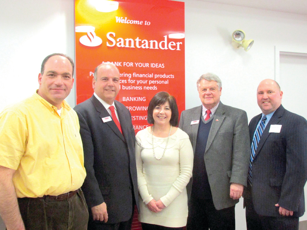 WARM WELCOME: Santander rolled out the red carpet for last Thursday's North Central Chamber of Commerce Business After Hours. Above, Senior Vice President Stephen Almagno, second left, Branch Manager Donald Baker, fourth left, and Senior Business Specialist Matthew Raiche, right, join NCCC Board Chair Randy Rauso, left, and President Deborah Ramos, center, in Johnston.