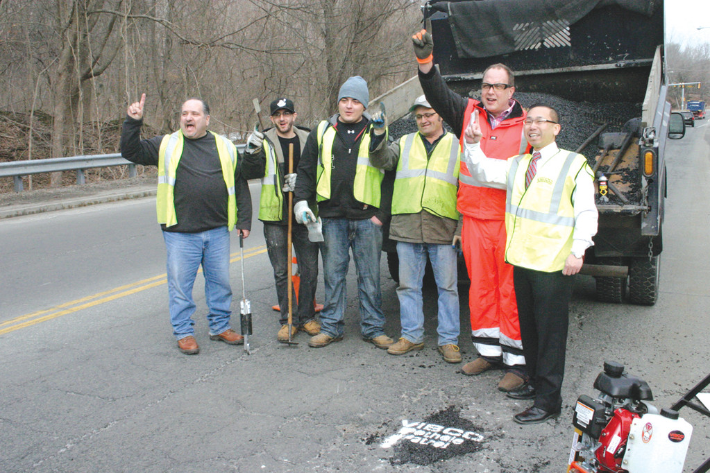 PATCHING THINGS UP: VIBCO Vibrators President Karl Wadensten, Cranston Mayor Allan Fung and Cranston highway personnel gather after a demonstration of VIBCO's vibratory roller.