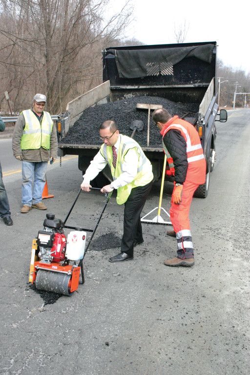 LIVE DEMONSTRATION: Cranston Mayor Allan Fung uses VIBCO's vibratory roller to patch a pothole on Natick Avenue.