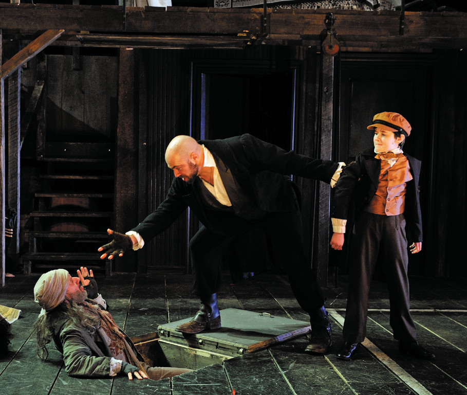 "Stephen Berenson as Fagin, Timothy John Smith as Bil Sikes and Phineas Peters as Oliver in ""Oliver!,"" book, Now playing through March 30 at Trinity Rep. Set design by Eugene Lee, costume design by William Lane, lighting design by Brian Lilienthal. (Photo by Mark Turek)"
