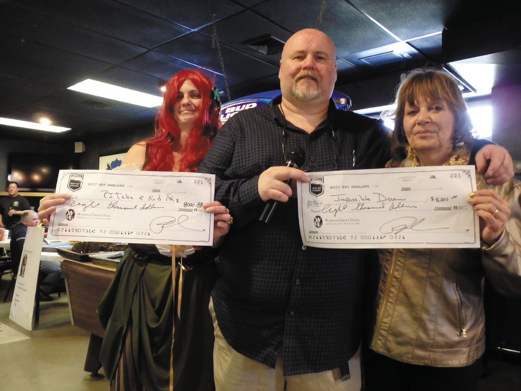 West Bay Anglers raise $16,000:  Pam Tameo (left, in costume with wig) from the West Bay Anglers foundation, and Dianne Florio-Penza (right), executive director of Impossible Dream,  each accept a $8,000 check from Pat Gallien, president of the West Bay Anglers.