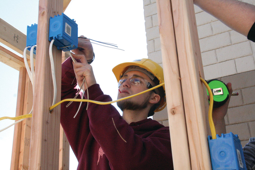 ELECTRIFYING: Senior Jared Connors from Warwick Area Career and Tech Center completes electrical work on the structure during competition.