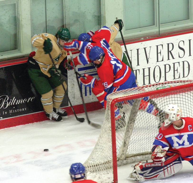 FIGHTING ON: Liam Watkinson tries to keep control of the puck while under pressure from two Mounties behind the net during Monday�s game three.