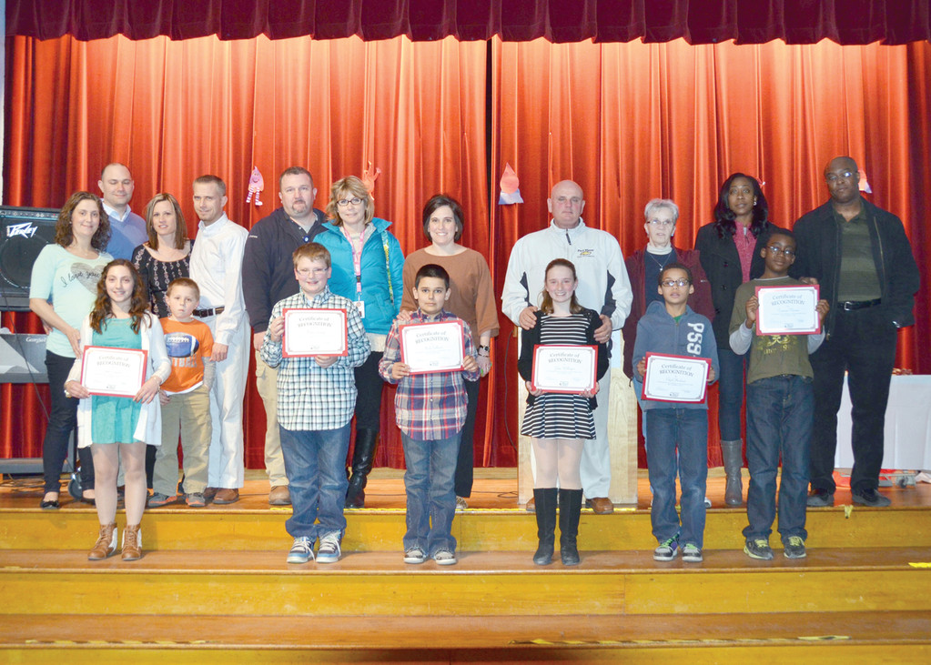 WINNERS TAKE STAGE: Essay winners from left, first row are Skyla Contarino, Nathan Rainey, Noah Sullivan, Jayln Wellington, Elijah Howland, and Temitope Olrainde. Parents are behind the students.
