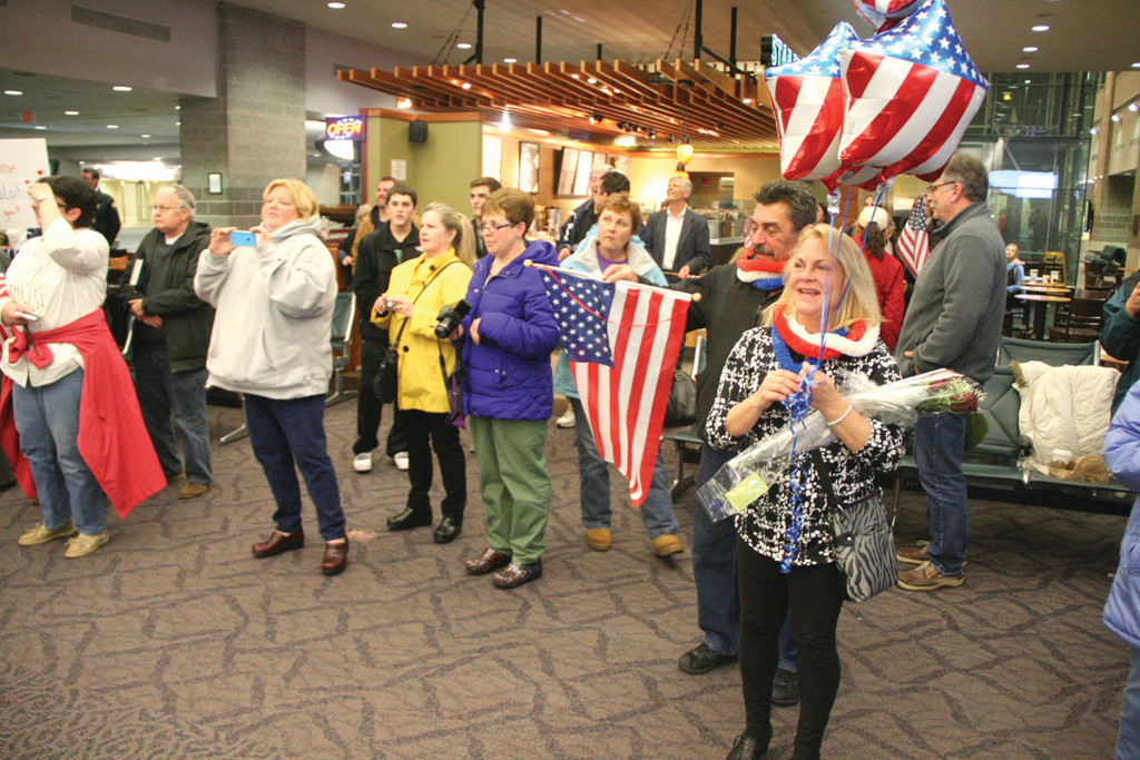 CHEERING THEIR RETURN: Matt Baron and Beth Gauthier, at right, joined friends and family greeting WWII veterans who visited war memorials in Washington during Saturday�s Honor Fight.